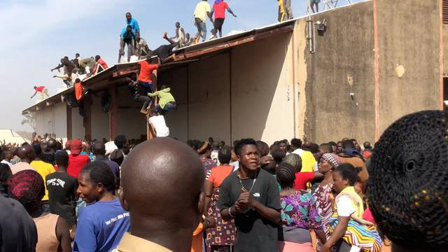 People gather around a warehouse in Bukuru