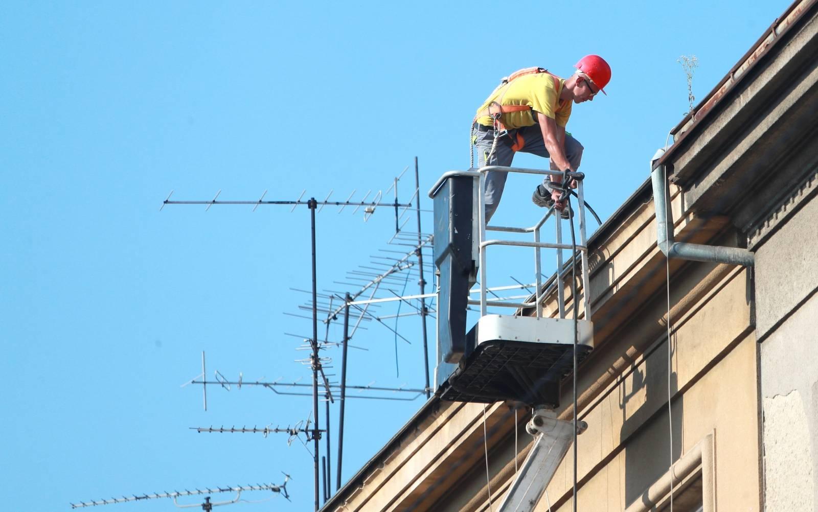 Zagreb: Radnik u košari dizalice sanira krov zgrade