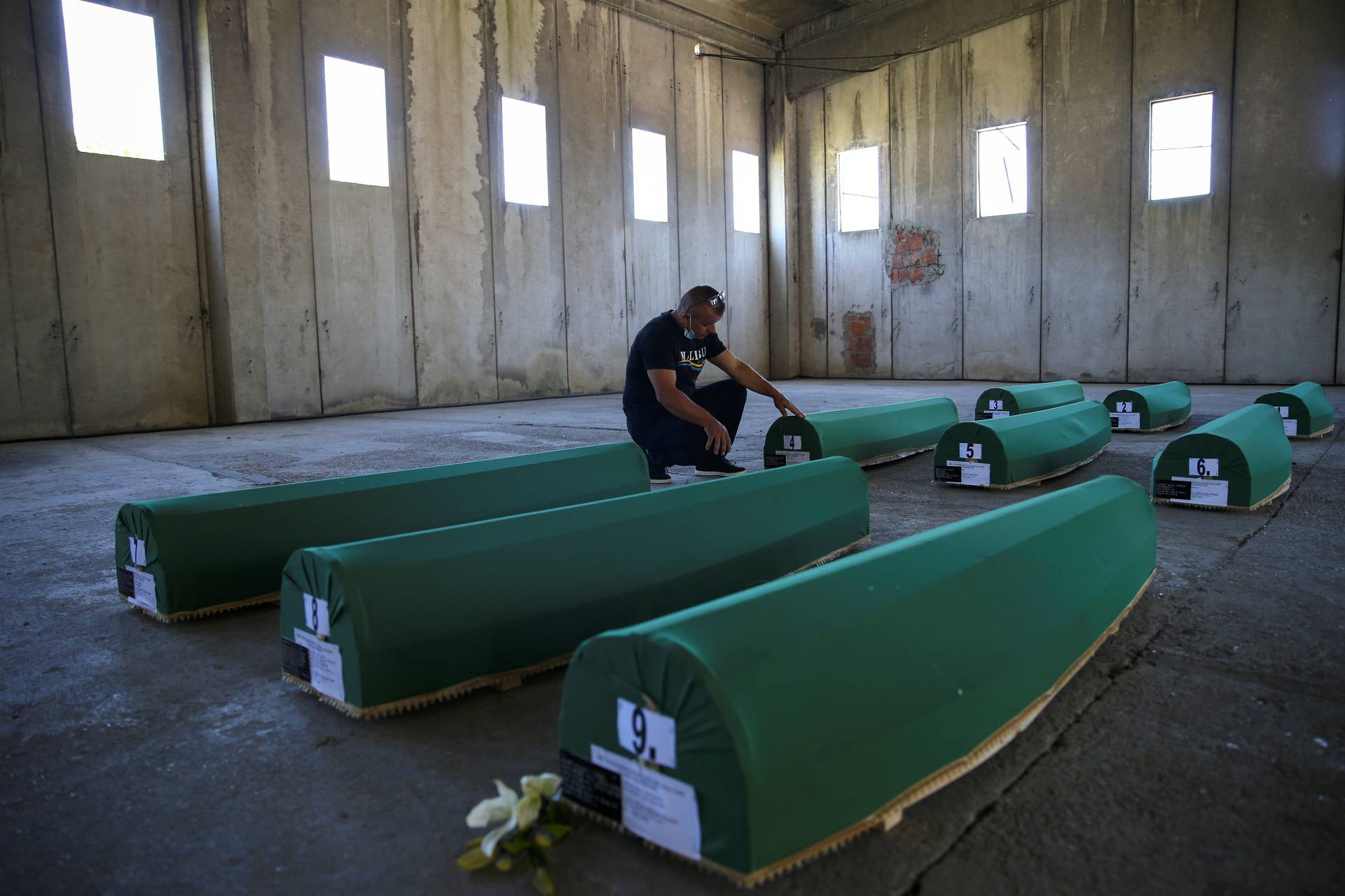 Bahrudin Salkovic, who lost his father, reacts next to the coffins with remains of newly identified victims at Potocari-Srebrenica Memorial ahead of burial on July 11, in Potocari