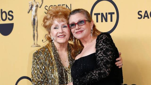 FILE PHOTO: Actress Debbie Reynolds poses with her daughter actress Carrie Fisher backstage after accepting her Lifetime Achievement award at the 21st annual Screen Actors Guild Awards in Los Angeles