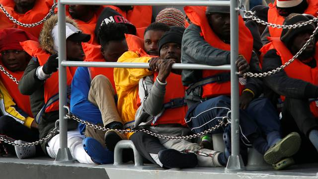 Migrants who were stranded on the German NGO Sea-Eye migrant rescue ship Alan Kurdi are seen before disembarking from an Armed Forces of Malta patrol boat at its base in Marsamxett Harbour, Valletta