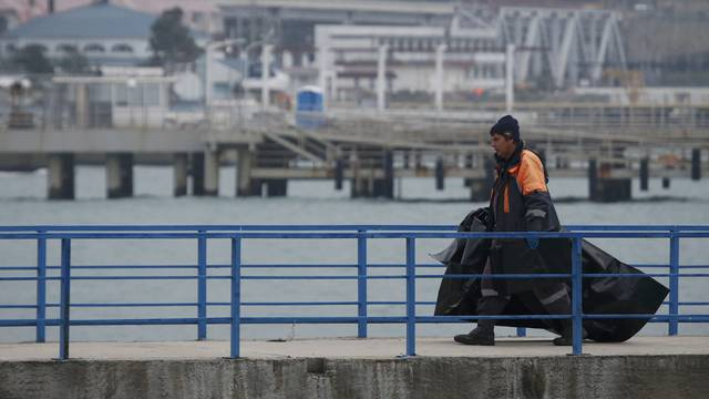 Russian Emergencies Ministry member carries plastic bags while walking on pier near crash site of Russian military Tu-154 plane in Black Sea in Sochi suburb of Khosta