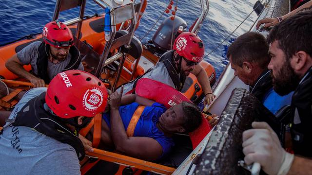 NBA Memphis player Marc Gasol and members of NGO Proactiva Open Arms rescue boat carry an African migrant in central Mediterranean Sea