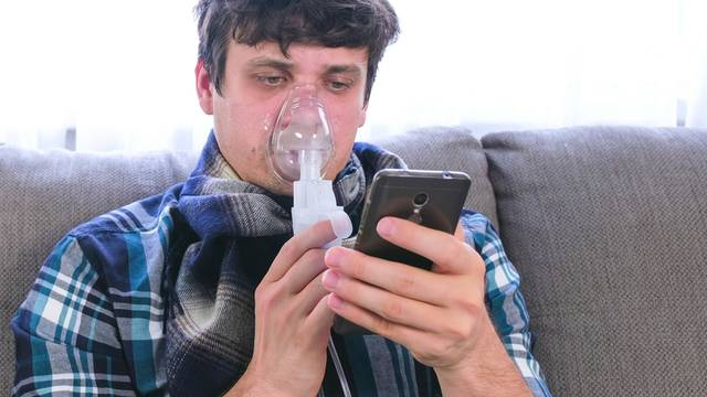 Use nebulizer and inhaler for the treatment. Sick man inhaling through inhaler mask and looking at mobile phone sitting on the sofa.