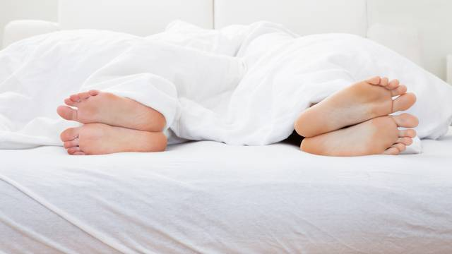 Close-up of couple's feet sleeping on bed