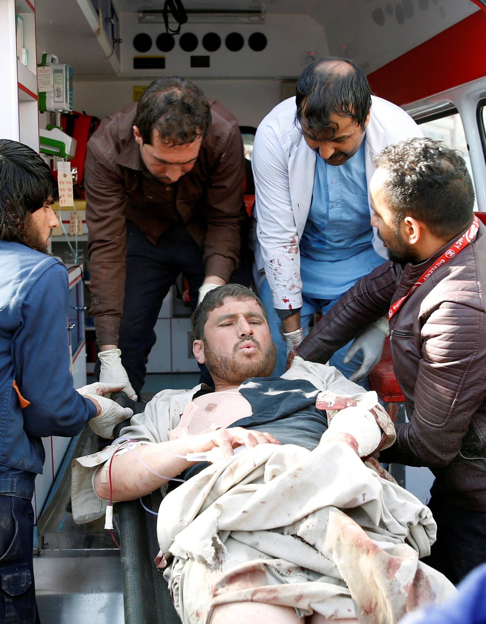 People carry an injured man to a hospital after a blast in Kabul