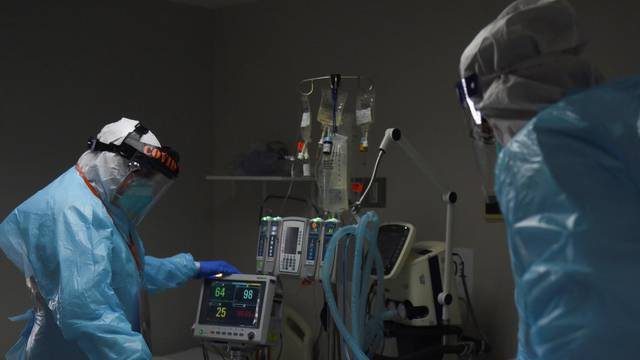 Dr. Joseph Varon and a healthcare worker check on a patient, at United Memorial Medical Center in Houston