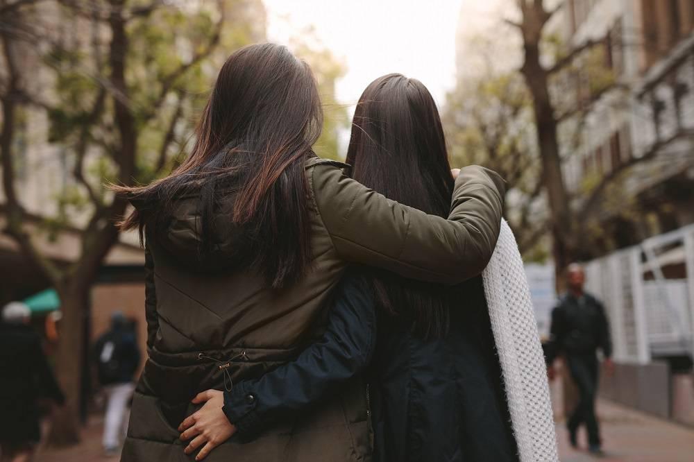 Rear view of two women walking on street