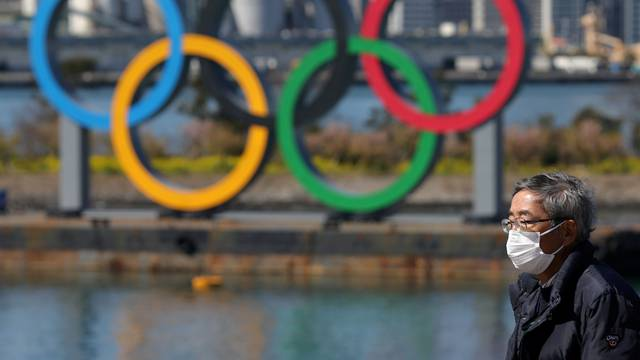 FILE PHOTO: A man walks in front of the Olympic rings at the waterfront area at Odaiba Marine Park in Tokyo