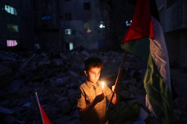 A boy holds a candle at the site of a house that was destroyed by Israeli air strikes during the Israeli-Palestinian fighting, in Gaza