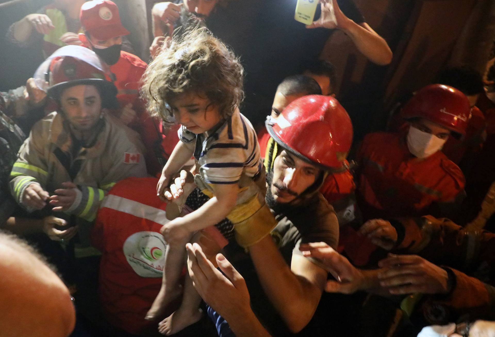 Rescuers carry a child that was evacuated from a building after a fuel tank exploded in the al-Tariq al-Jadida neighborhood of Beirut