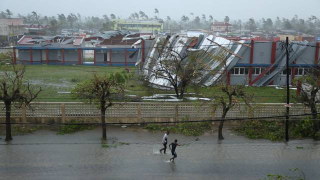 People walk down a flooded road next to buildings damaged by Cyclone Idai in Beira