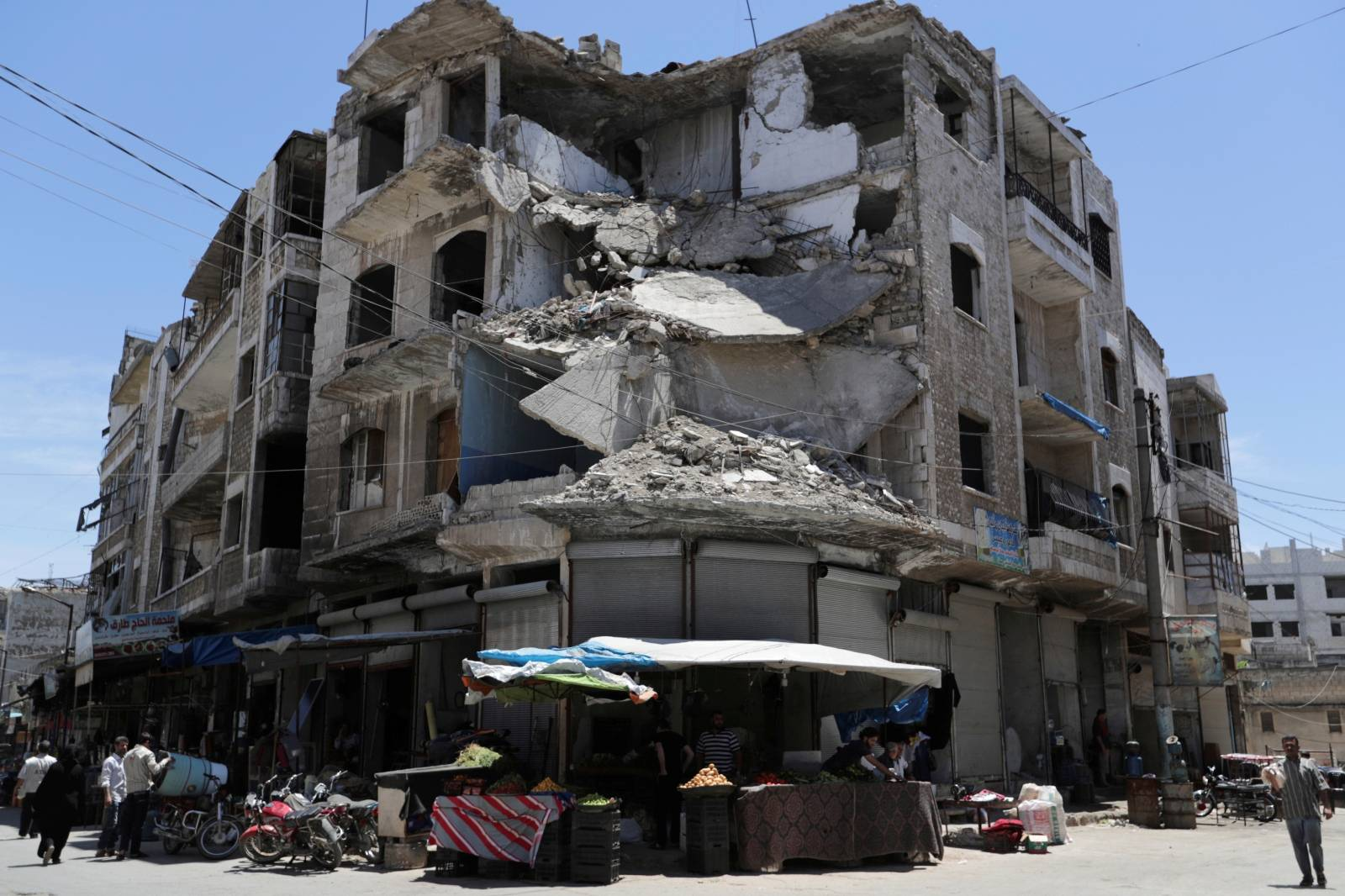 FILE PHOTO: People walk past a damaged building in the city of Idlib