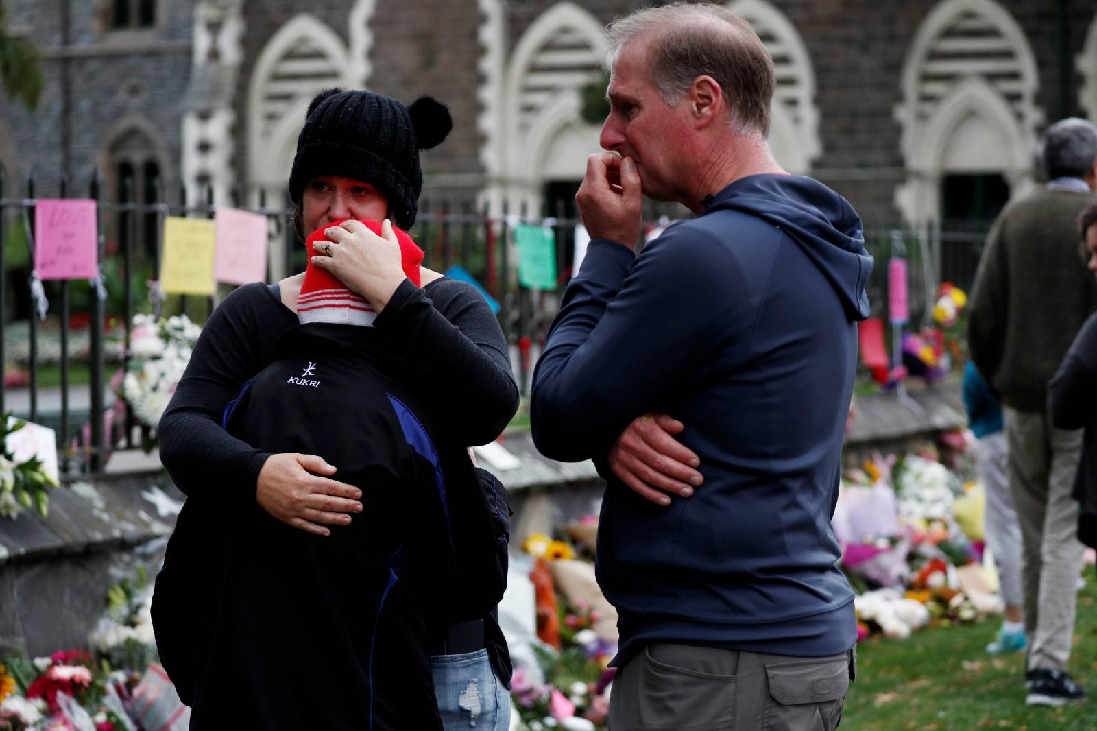 People react at a flower tribute area at Botanical Gardens in Christchurch