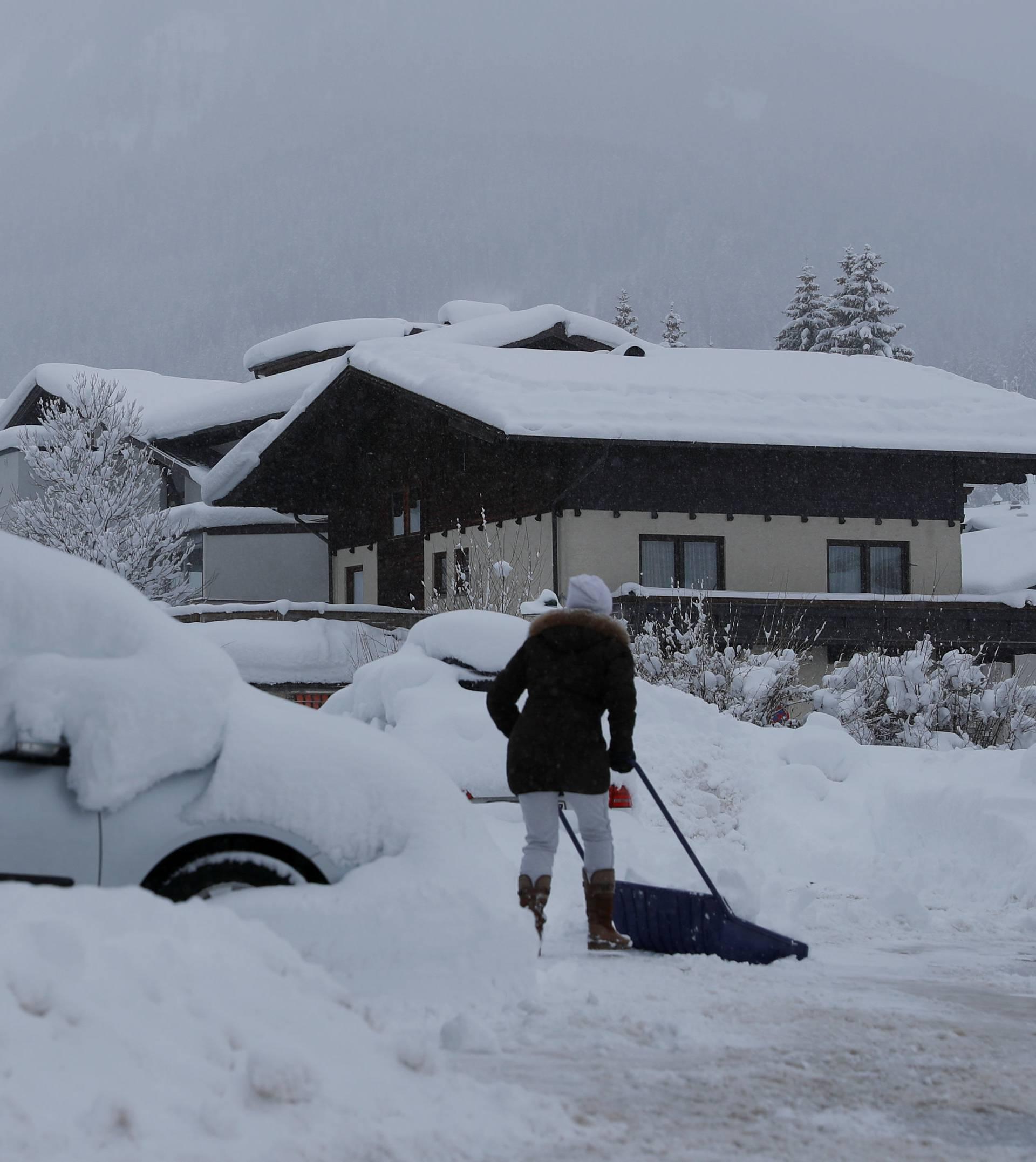 A woman shovels snow on a road after heavy snowfall in Flachau