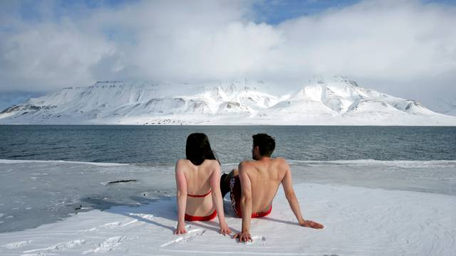 "FILE PHOTO: Climate activists Lesley Butler and Rob Bell ""sunbathe"" on the edge of a frozen fjord in the Norwegian Arctic town of Longyearbyen"