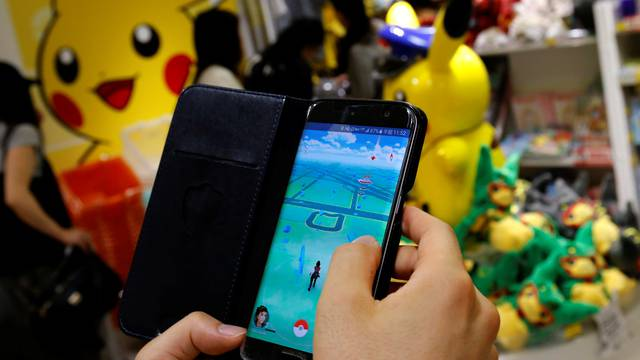 """A man plays the augmented reality mobile game """"Pokemon Go"""" by Nintendo in front of a shop selling Pokemon goods in Tokyo"""