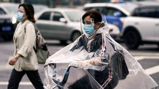 People wearing protective face masks are seen on a street in Wuhan