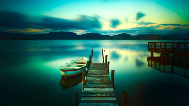 Wooden pier or jetty and a boat on a lake sunset. Versilia Tusca