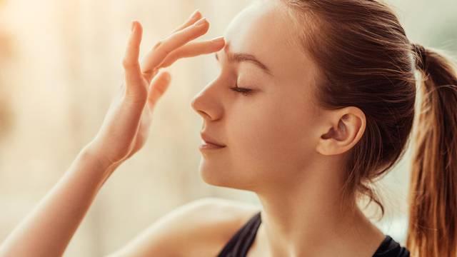 Young woman massaging third eye chakra