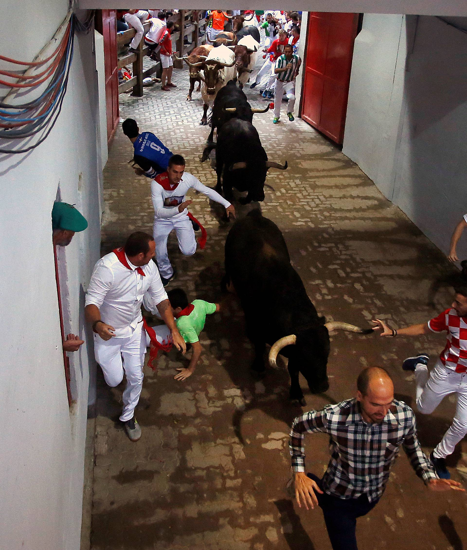 Runners sprint ahead of Fuente Ymbro fighting  bulls during the fourth running of the bulls at the San Fermin festival in Pamplona