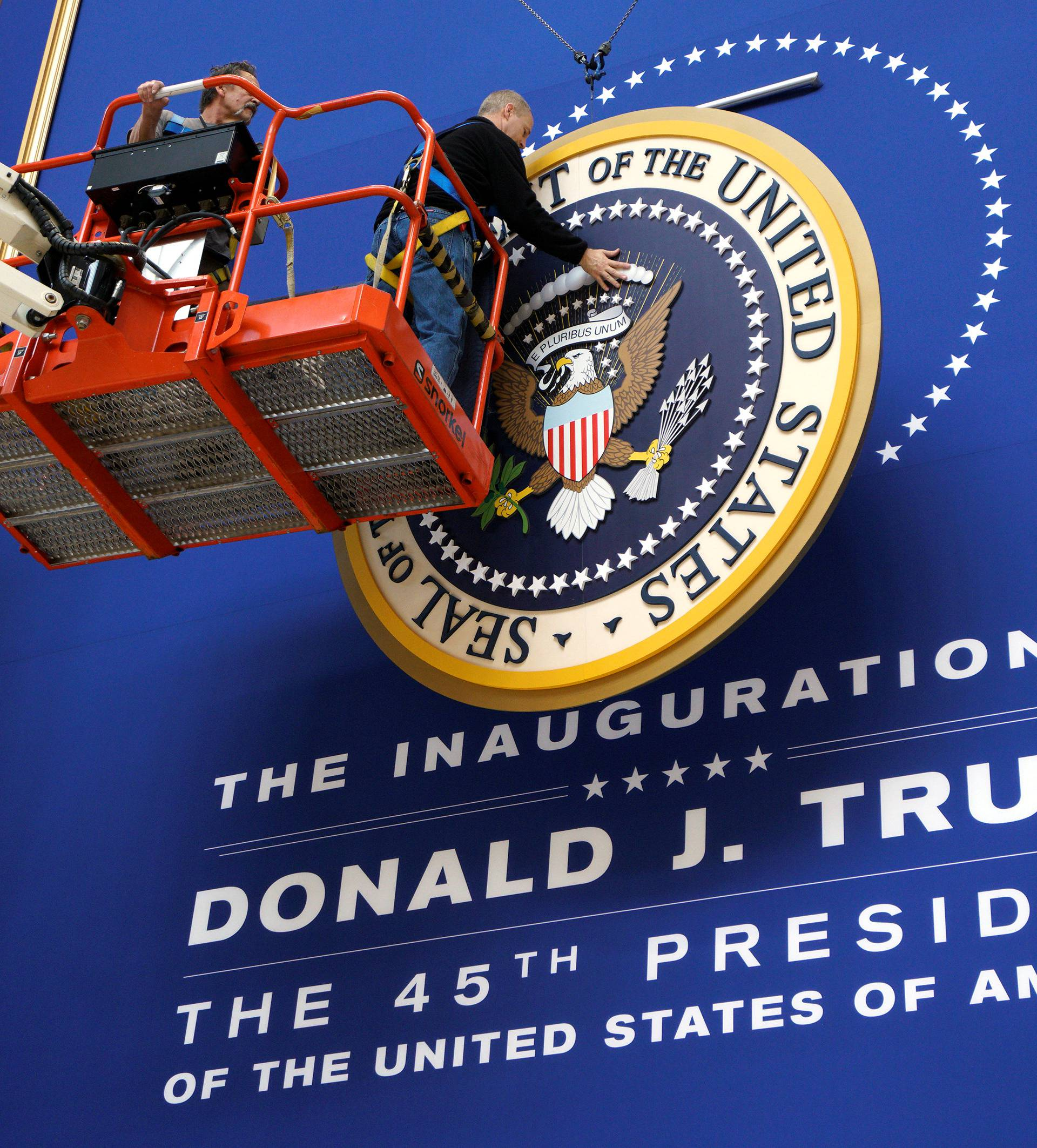 Workers install the presidential seal at the site of the Commander in Chief inaugural ball for President-elect Donald Trump in Washington, DC