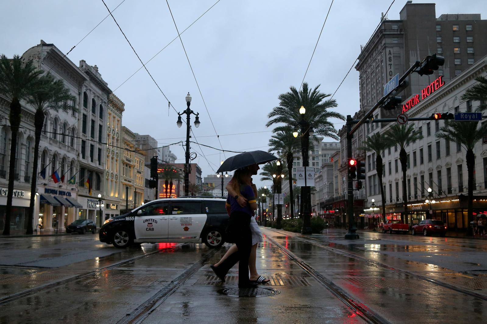 A couple walks across Canal St. during Hurricane Barry in New Orleans