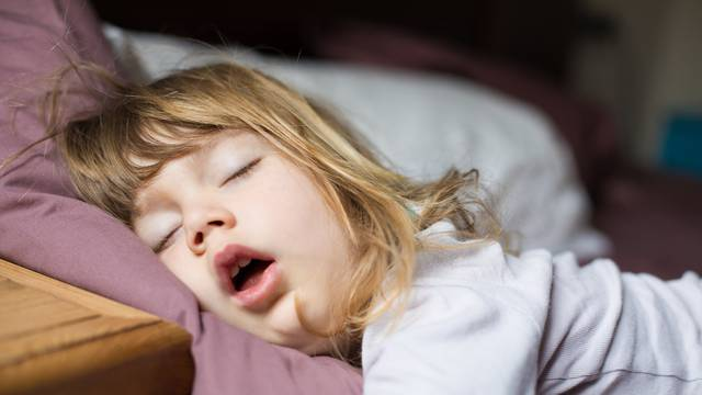 funny face of child sleeping on king bed