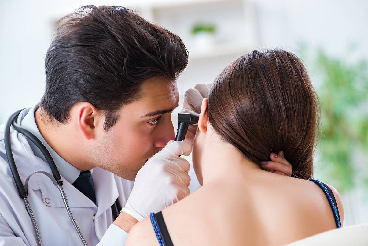 The doctor checking patients ear during medical examination