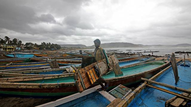 A fisherman carries his tools as he leaves for a safer place after tying his boats along the shore ahead of cyclone Fani in Peda Jalaripeta on the outskirts of Visakhapatnam
