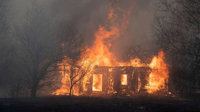 FILE PHOTO: A view shows a wooden house on fire in Lyudvynivka in Kiev Region