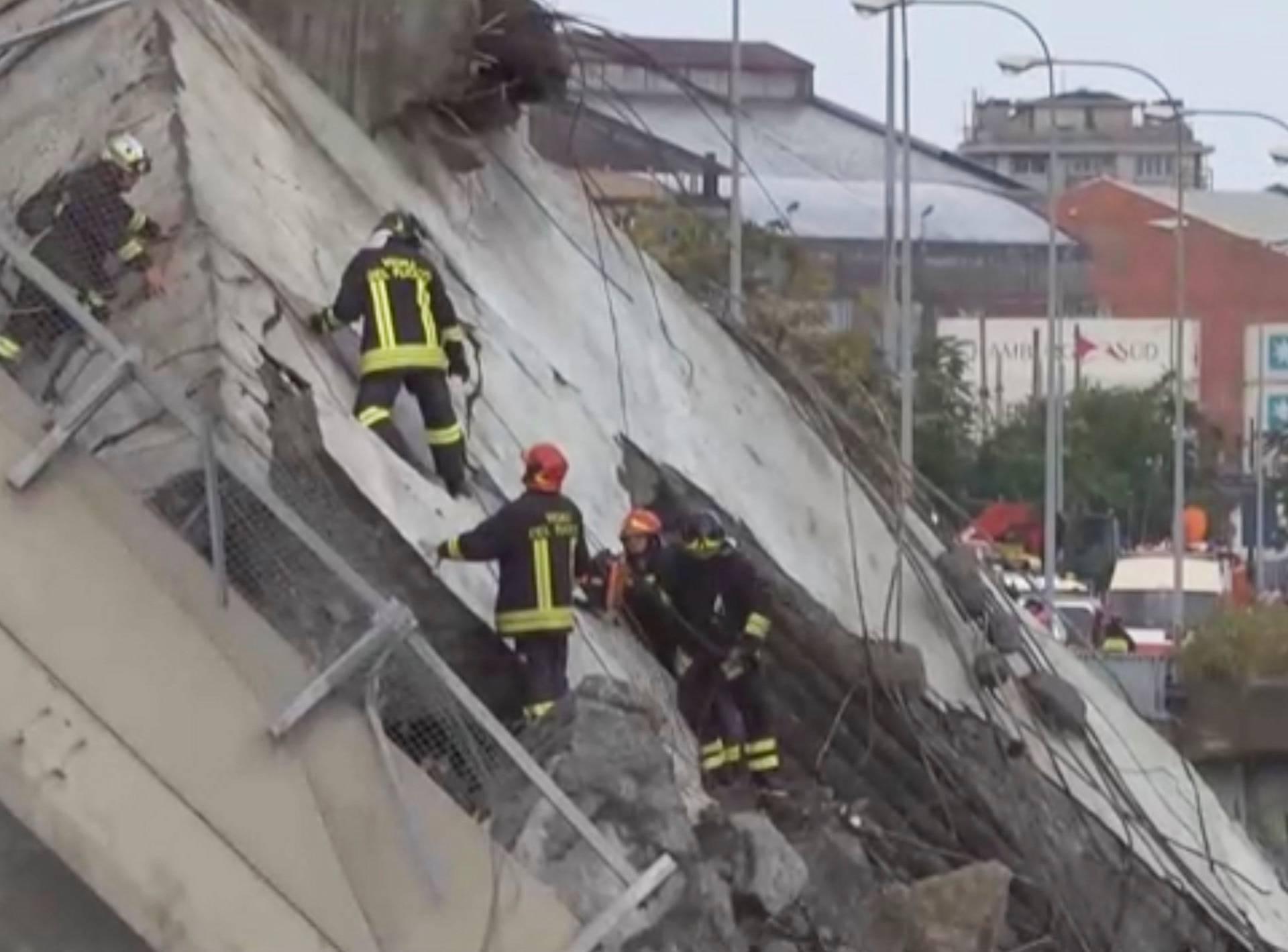 Rescue workers are seen at the collapsed Morandi Bridge in the Italian port city of Genoa