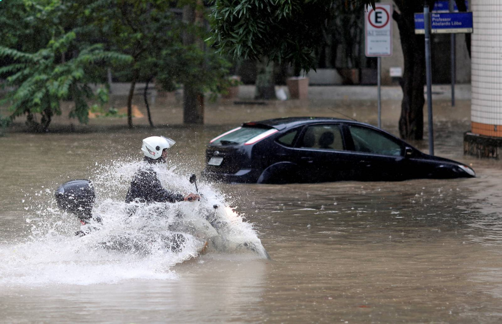 A man drives his motorbike during floods after heavy rains, in Humaita neighbourhood, Rio de Janeiro