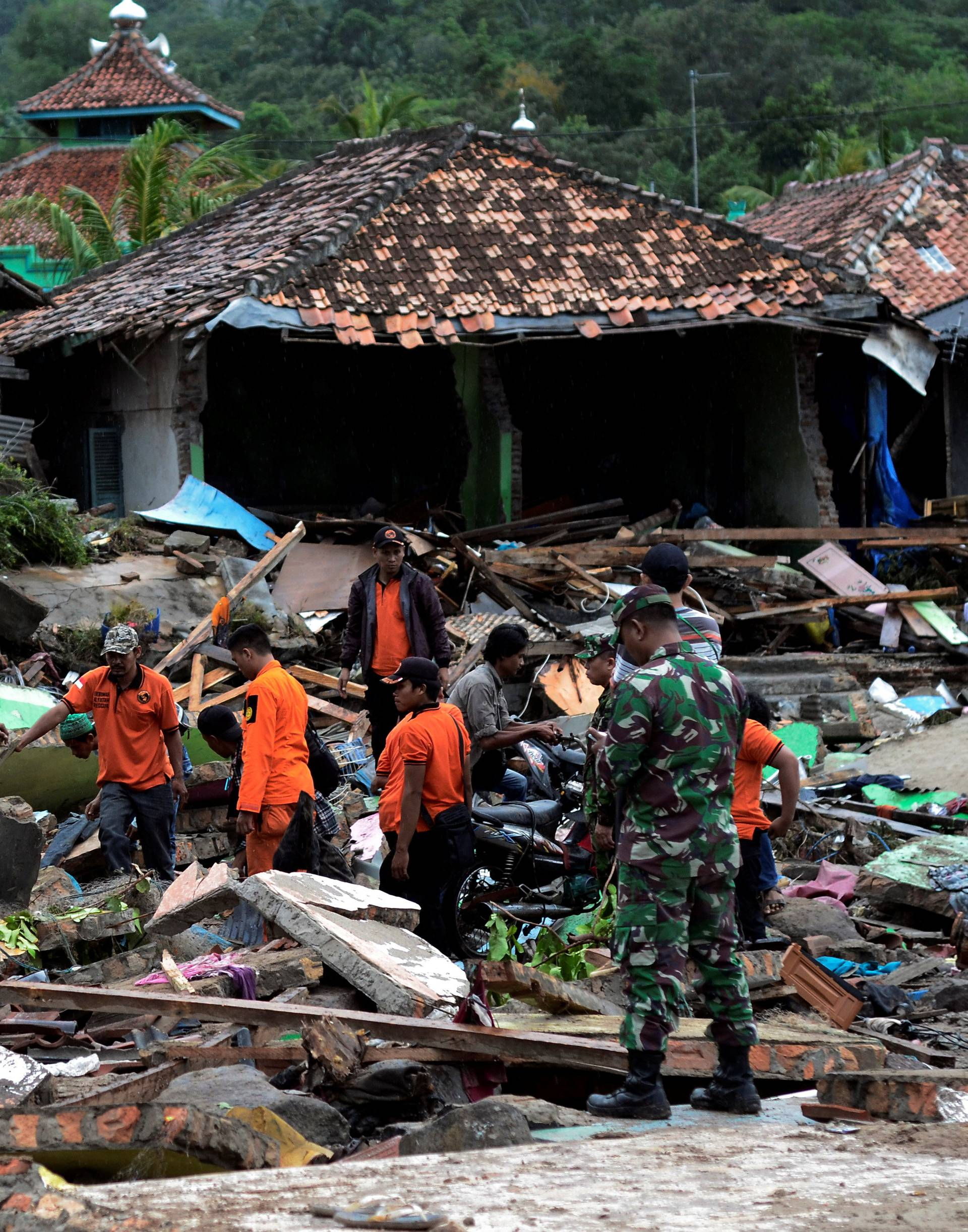 Rescue team members search for victims among debris after a tsunami hit at Rajabasa district in South Lampung