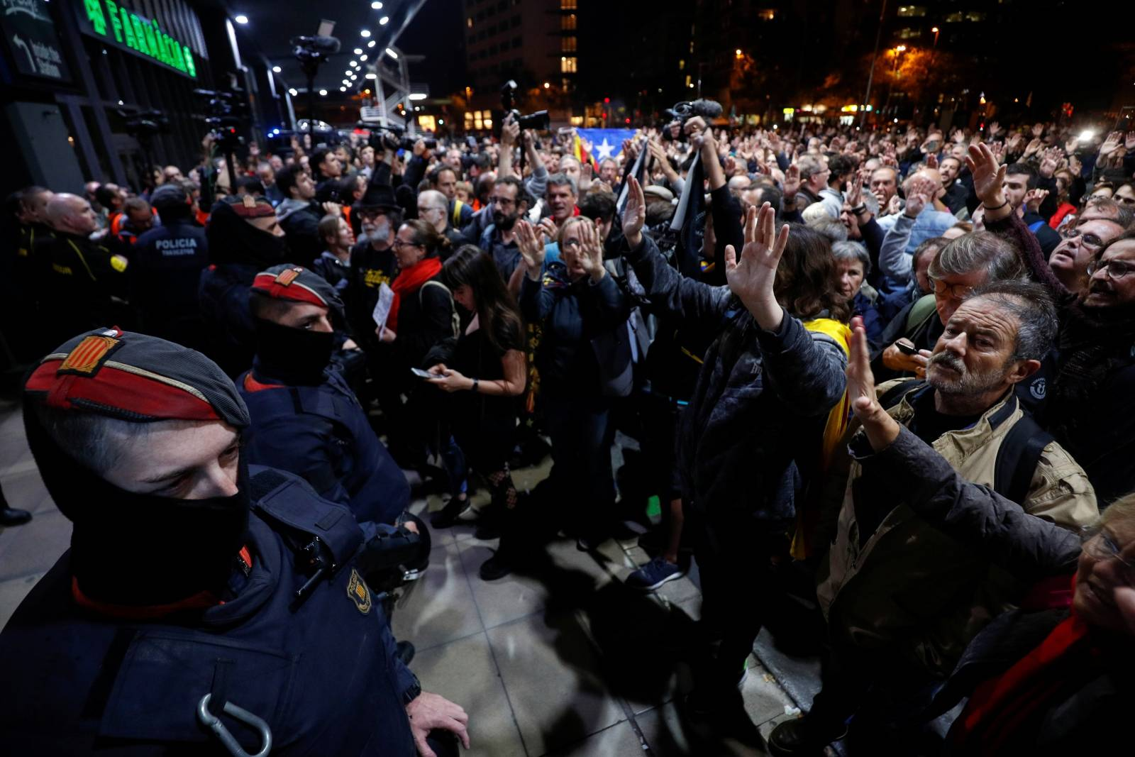 People participate in a protest as security forces stand guard outside the Sants train station in Barcelona