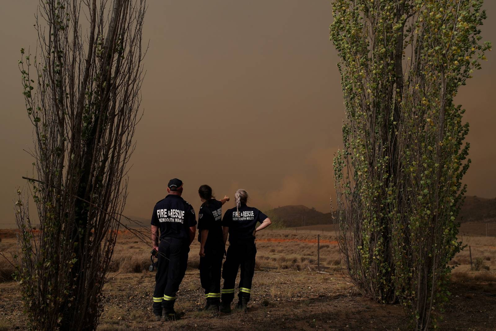 Personnel from Fire and Rescue NSW monitor a bushfire as it approaches a home in Bredbo