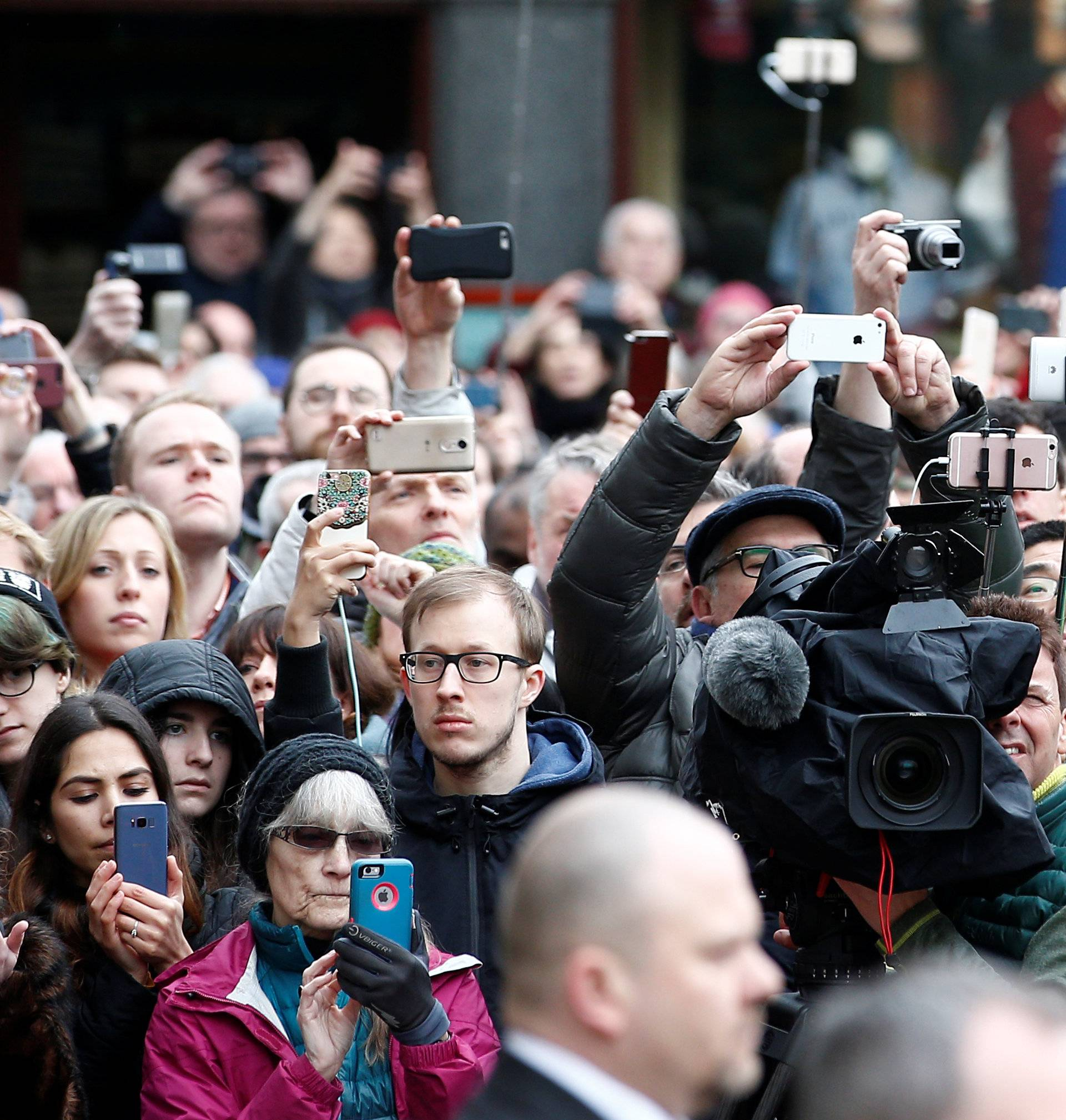 Members of the public and media photograph the funeral cortege as it arrives at Great St Marys Church, where the funeral of theoretical physicist Prof Stephen Hawking is being held, in Cambridge