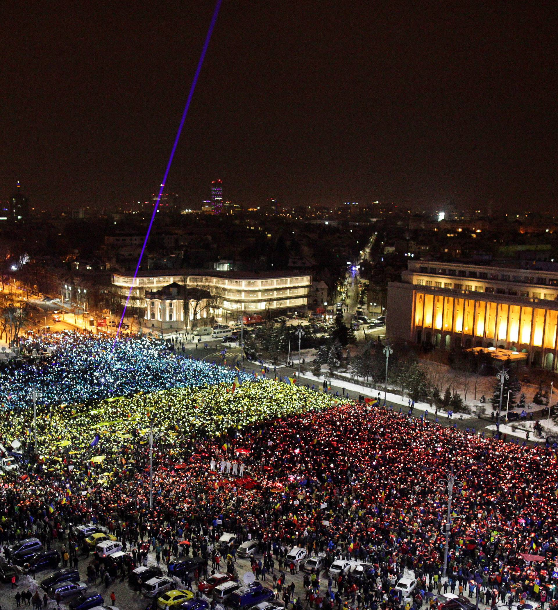 Protesters display the Romanian national flag colours during a demonstration in front of the government building in Bucharest