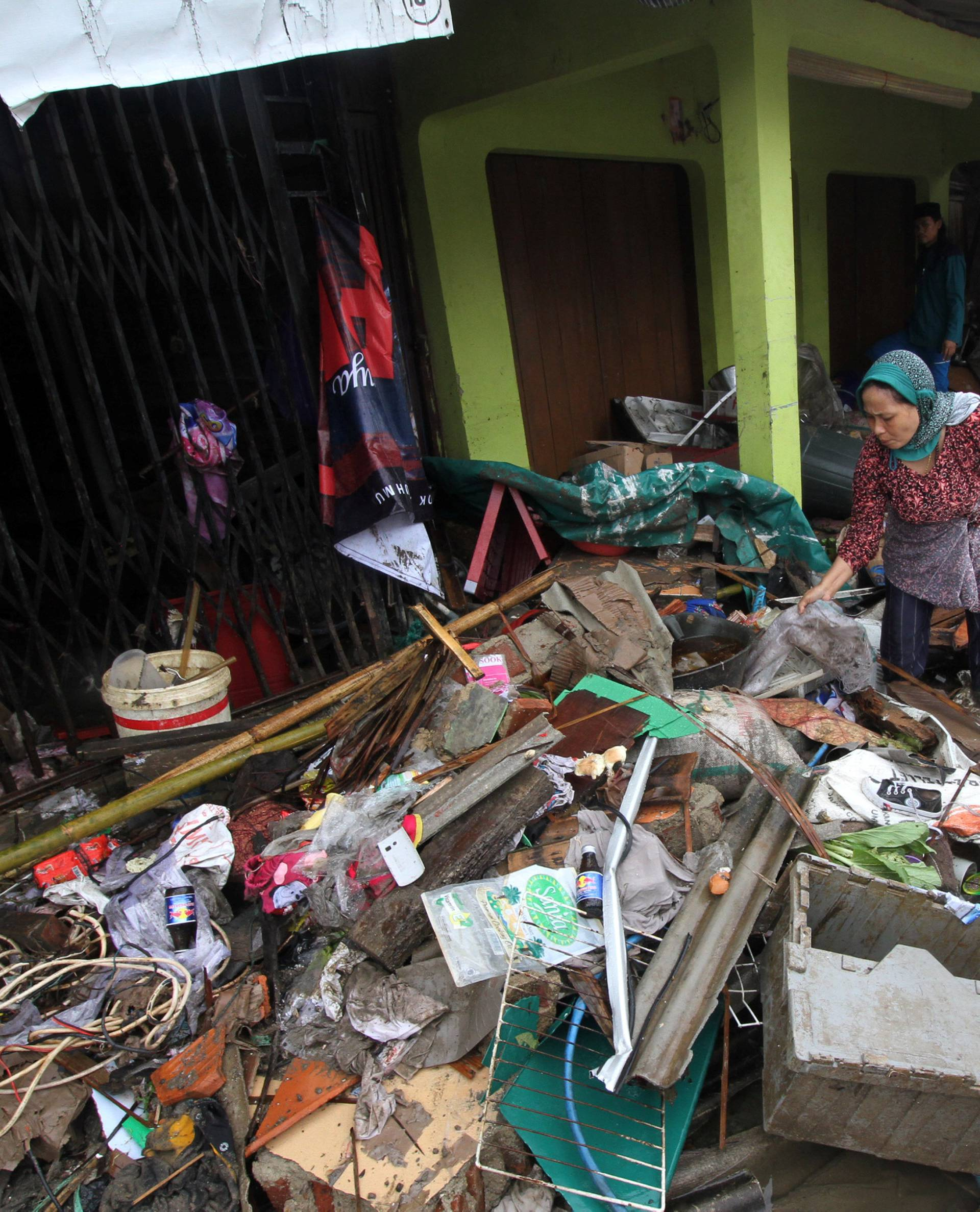 A local resident searches for her items after a tsunami hit at Sumur district in Pandeglang