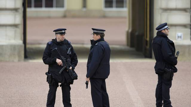 Armed police officers stand on duty at Buckingham Palace in London