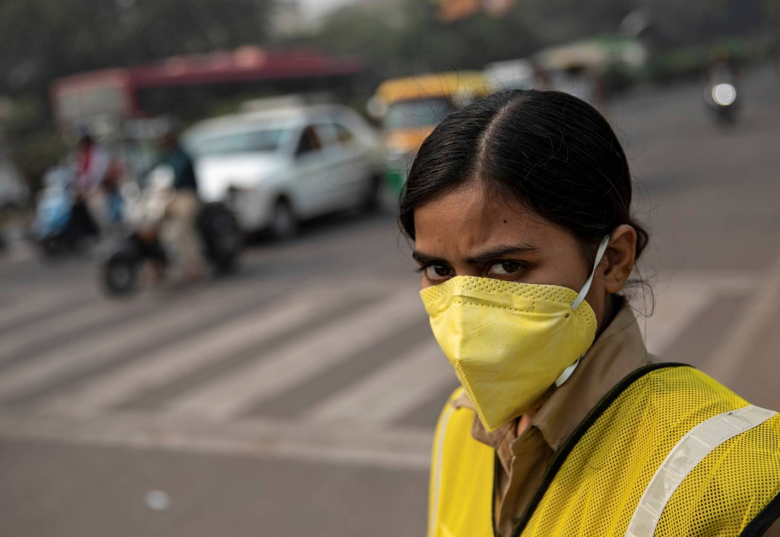 A policewoman wears a mask to protect herself from air pollution at a junction during restrictions on private vehicles based on registration plates on a smoggy morning in New Delhi