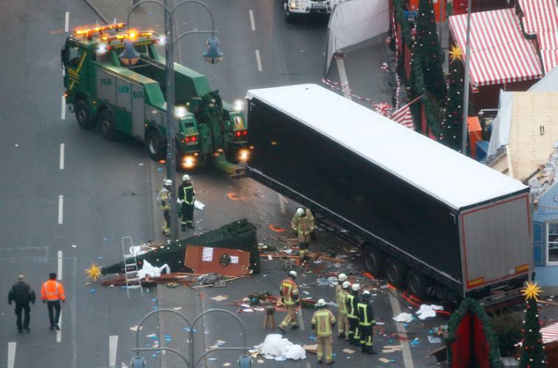 Rescue workers tow the truck which ploughed into a crowded Christmas market in the German capital last night in Berlin
