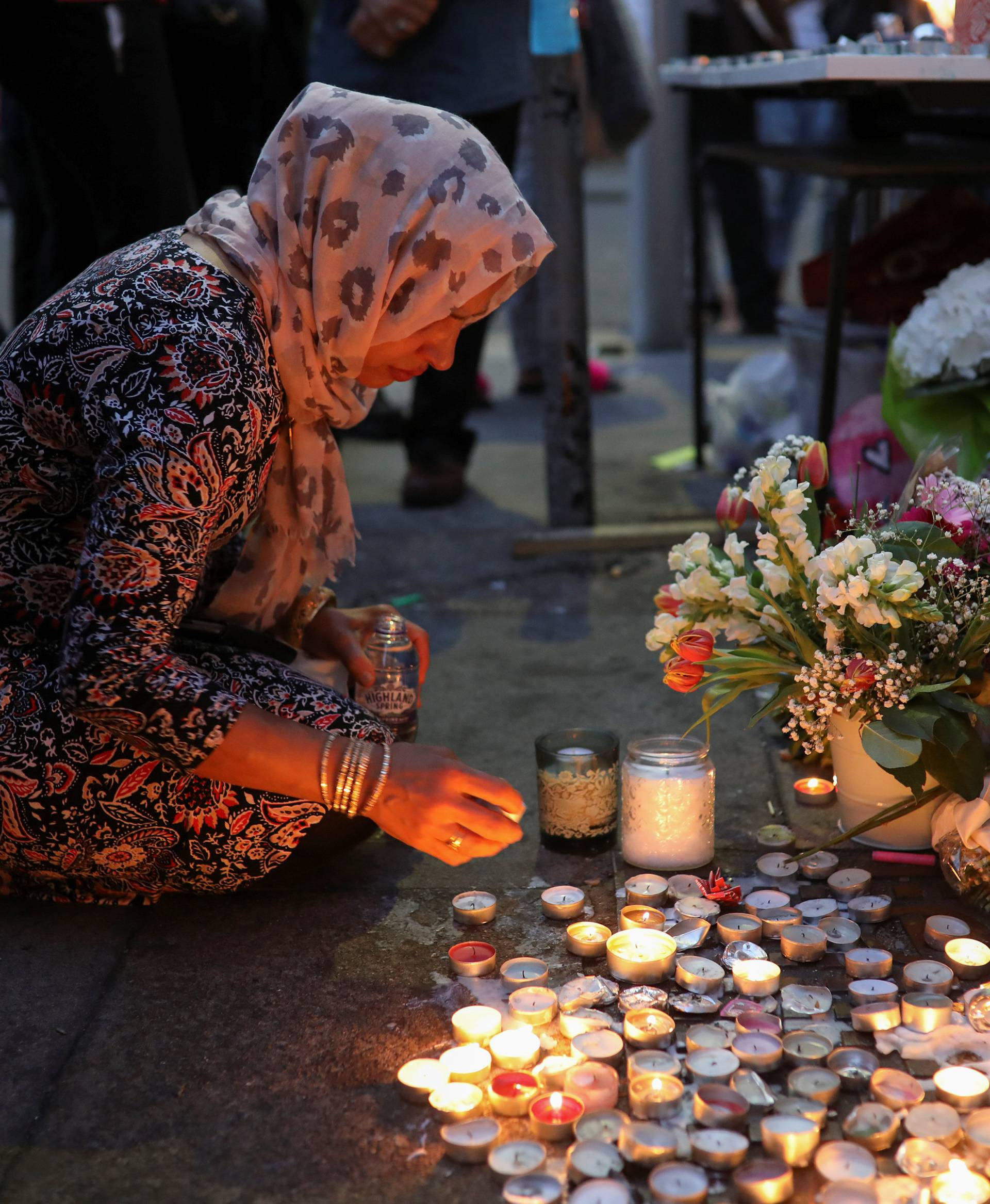 A woman lights a candle next to a wall covered with tributes to and pictures of the victims of the Grenfell apartment tower fire in North Kensington, London