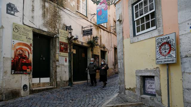 Two women walk in Alfama neighbourhood wearing protective masks during the coronavirus disease (COVID-19) pandemic in Lisbon