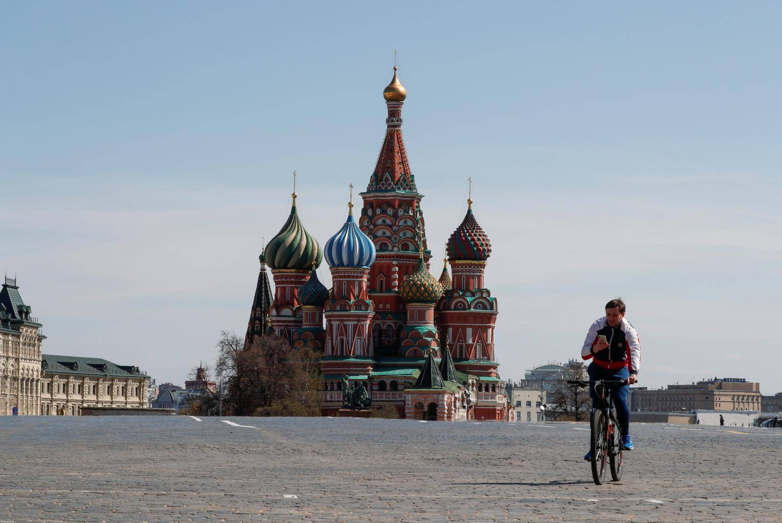 A man rides a bicycle along empty Red Square amid the coronavirus disease outbreak in Moscow