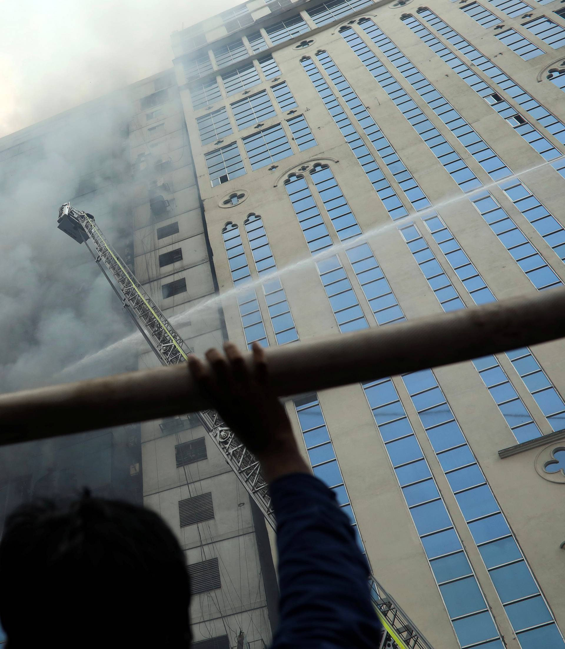 A person looks on as firefighters attempt to extinguish a fire at a multi-storey commercial building in Dhaka