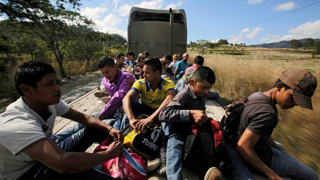 Hondurans, part of a new caravan of migrants travelling towards the United States, ride in a trailer as they hitch a ride in Cucuyagua