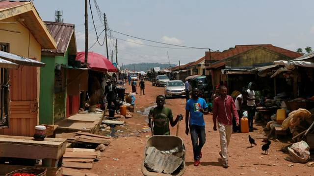 People walk along a street in Abuja