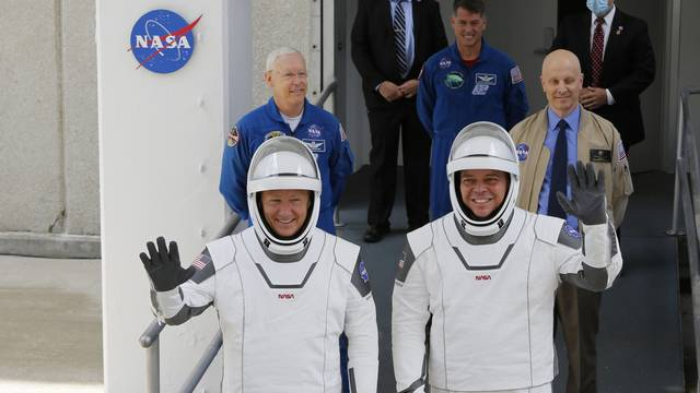 NASA astronauts Douglas Hurley and Robert Behnken wave as they head to Pad39A before the launch of a SpaceX Falcon 9 rocket and Crew Dragon spacecraft at the Kennedy Space Center, in Cape Canaveral