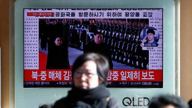 People watch a TV broadcasting a news report on North Korean leader Kim Jong Un's visit to China, in Seoul